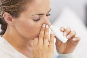 Женщина закапывает лекарство для носа